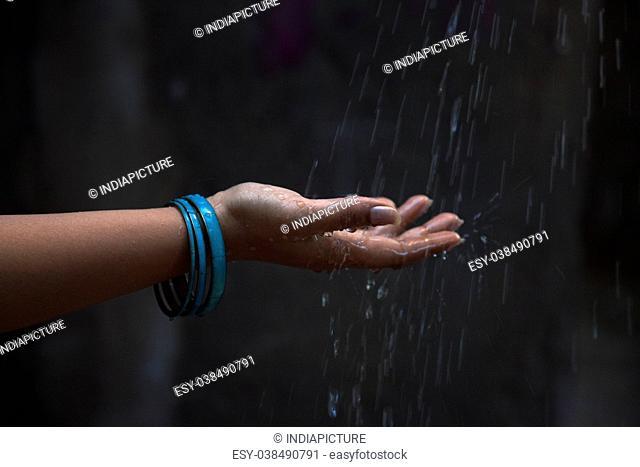 Woman with bangles enjoying rain in outdoor