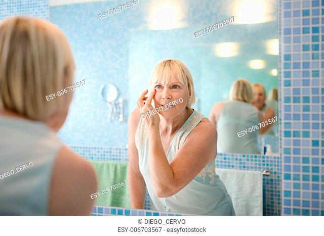 Female beauty, senior caucasian woman applying lotion on face in bathroom at home