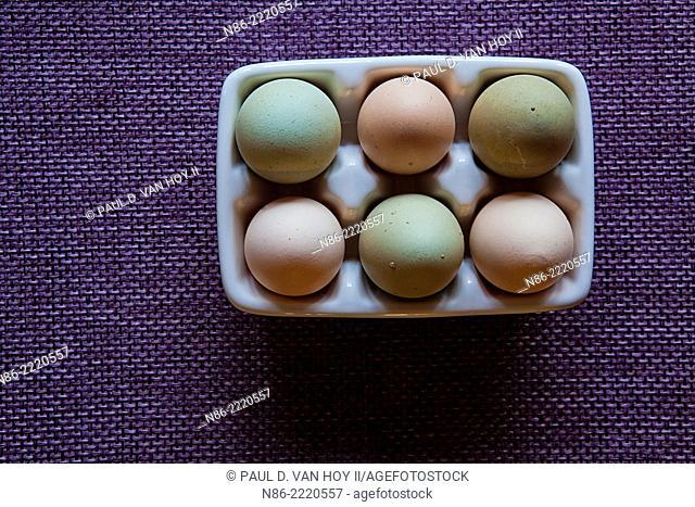 half a dozen free range eggs in a ceramic dish