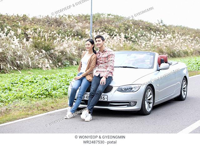Young smiling couple sitting on a car on a road
