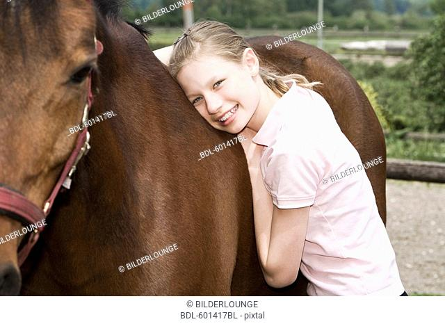 portrait of young girl with brown horse