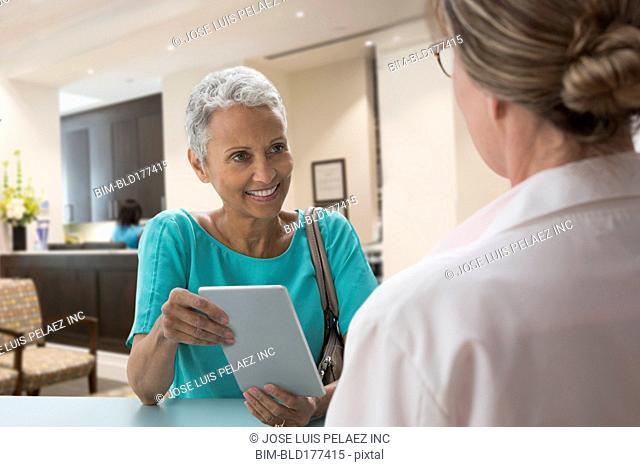 Woman holding digital tablet with doctor