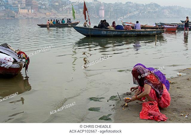 People worshipping and river boats on the Ganges River, Varanasi, formerly Benares, Uttar Pradesh, India