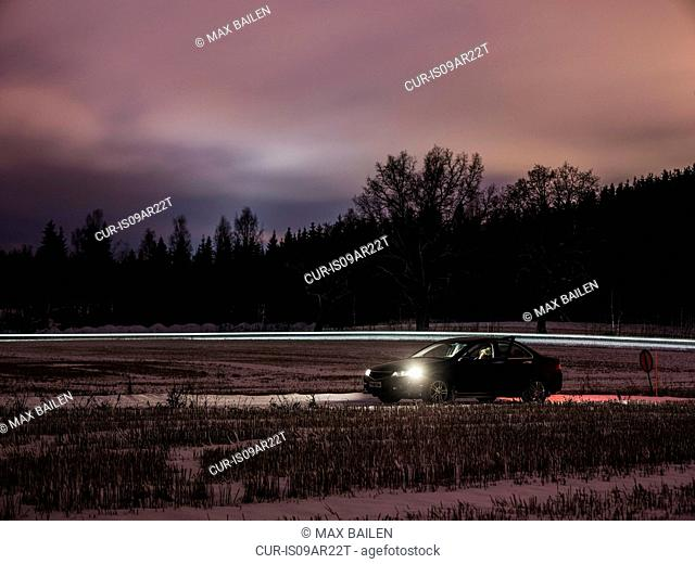 Woman sleeping in car parked on roadside at night, Lahti, Finland
