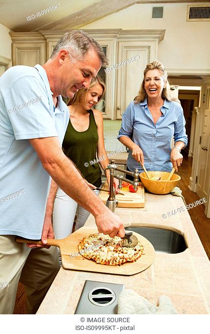 Family preparing pizza together in kitchen