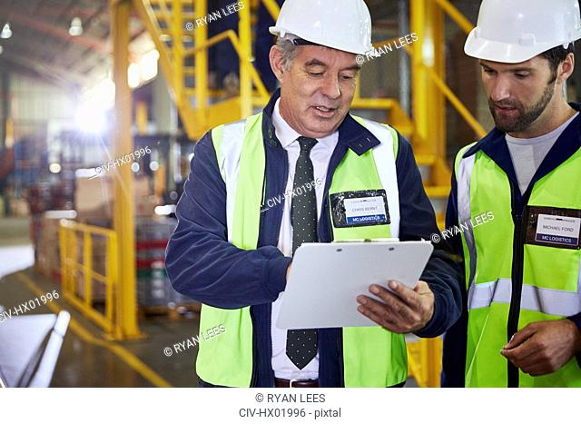 Manager and worker with clipboard meeting in distribution warehouse