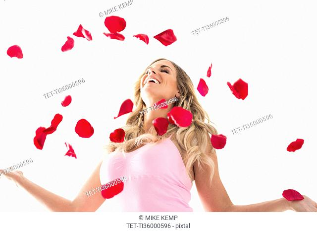 Young woman throwing up rose petals above head