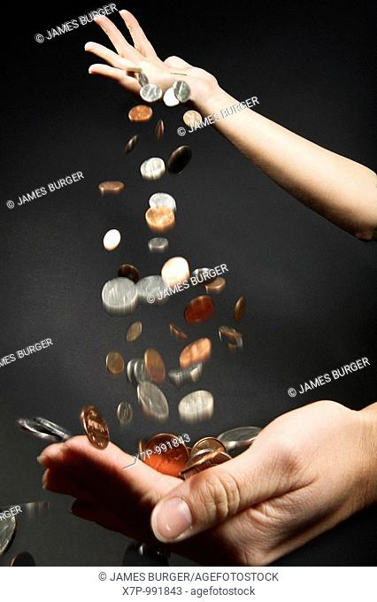 Coins dropping from one hand into another hand