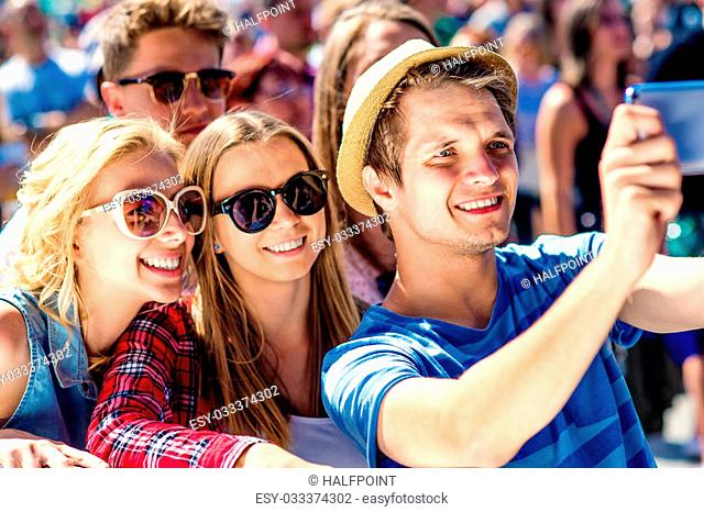 Teenagers at summer music festival in crowd taking selfie with smartphone, enjoying themselves
