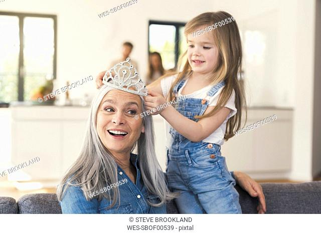 Granddaughter putting crown on grandmothes head