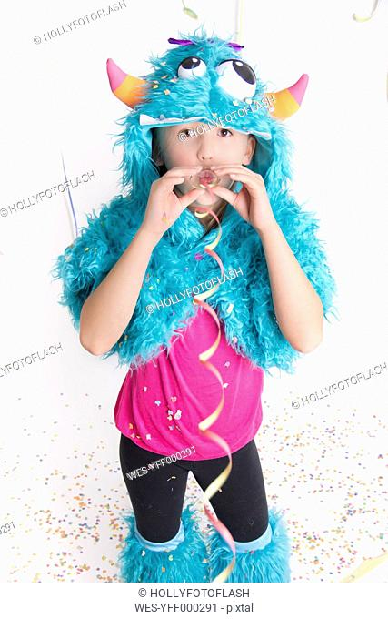 Girl masquerade as a monster standing in front of white background blowing streamer