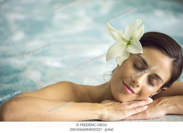 Woman in pool, resting head on arms