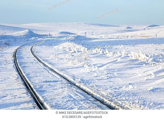 Railroad track carves a curve in the snow covered agricultural landscape of Eastern Washington