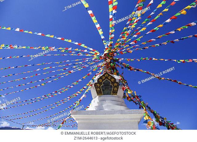 Stuppa near Sangri-La city , colorful flags in wind, Yunnan, tibetan style, China