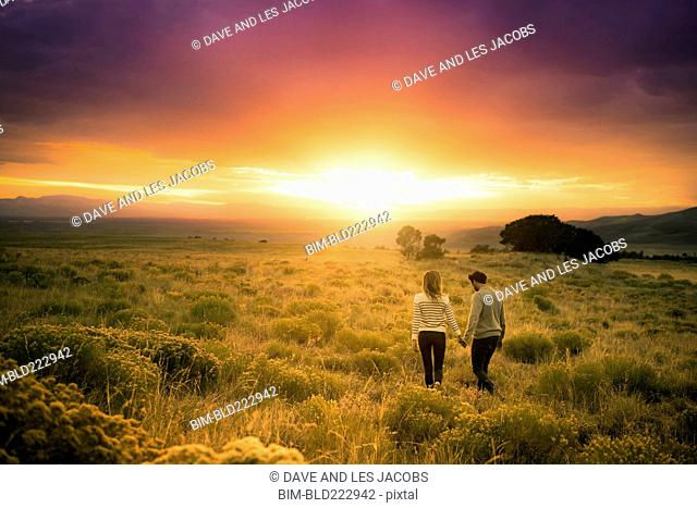 Hispanic couple holding hands in field at sunset