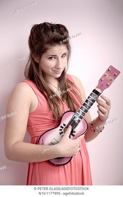 Teen girl playing a ukulele