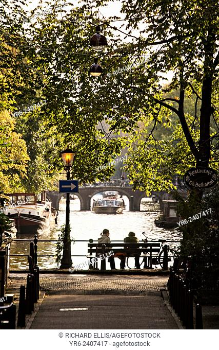 Couple on a bench at the Brouwersgracht where this canal crosses the Herengracht in Amsterdam