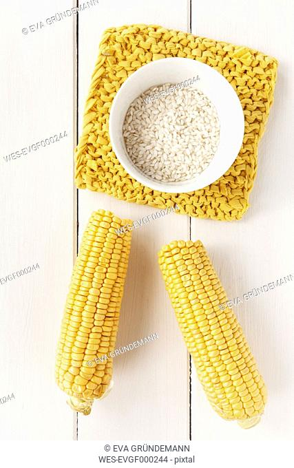 Sweetcorn cobs and arborio rice on white wooden table, studio shot