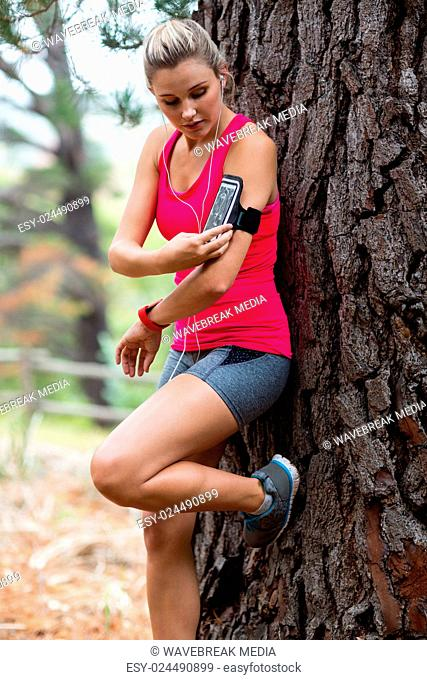 Woman changing music track on mobile phone