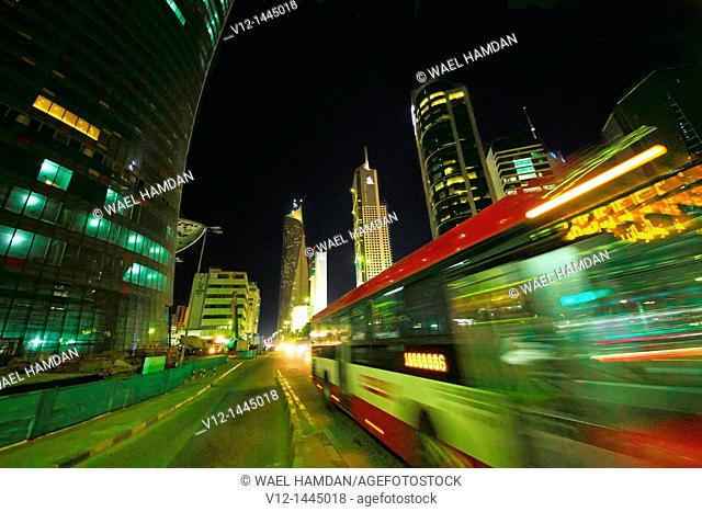 Public bus on the streets of downtown Kuwait City at night. Kuwait