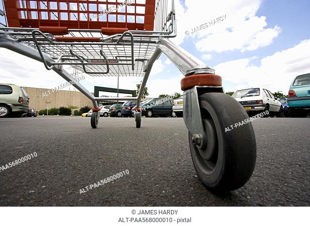 Shopping cart in parking lot, surface level view