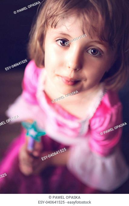 Little fairy princess looking up and holding small plastic magic wand