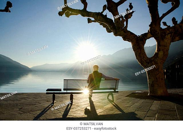 Man sitting on a bench and watching a sunset