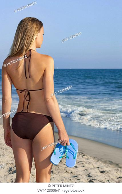 Women in bikini on beach overlooking the Pacific Ocean; Los Angeles, California, United States of America