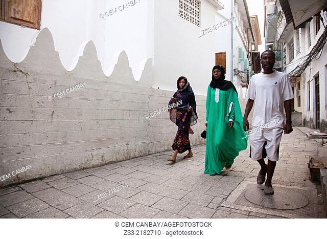 Muslim man and muslim women wearing headscarf near an old arabic-style wall, Stone Town, Unguja Island, Zanzibar Archipelago, Tanzania, East Africa
