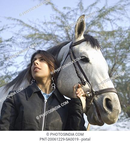 Young woman standing with a horse