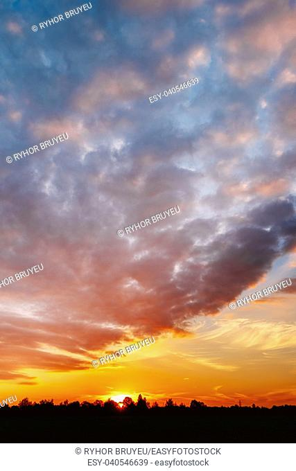 Natural Sunset, Sunrise Over Forest. Bright Dramatic Sky And Dark Ground. Countryside Landscape Under Scenic Summer Dramatic Sky In Sunset Dawn Sunrise