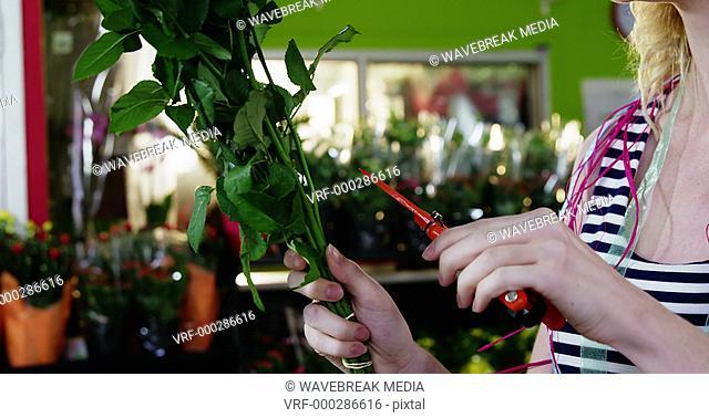 Smiling female florist trimming flower stem in flower shop