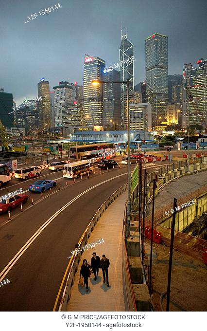 people and traffic pass through Central Hong Kong construction zone at dusk