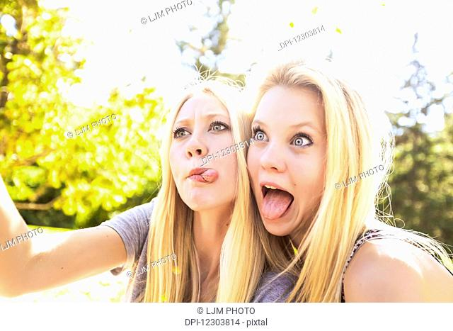 Two sisters having fun outdoors in a city park in autumn taking selfies of themselves and making funny faces; Edmonton, Alberta, Canada
