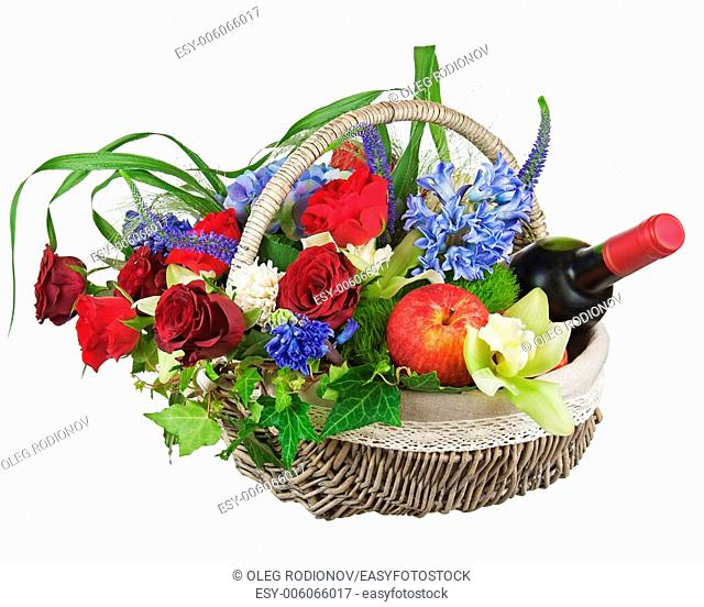 Flower arrangement of roses, orchids, fruits and bottle of wine isolated on white background