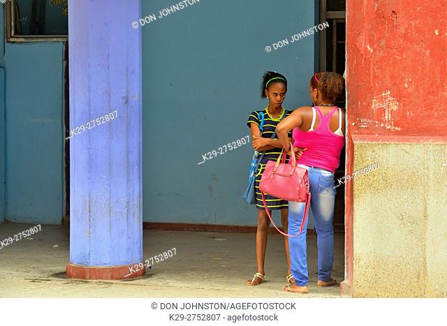 Street photography in central Havana- Two ladies conversing on the street, La Habana (Havana), Habana, Cuba