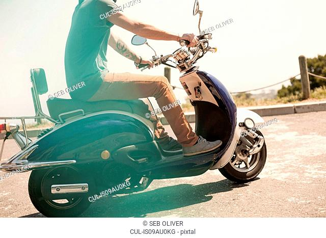 Mid adult man riding moped, low section