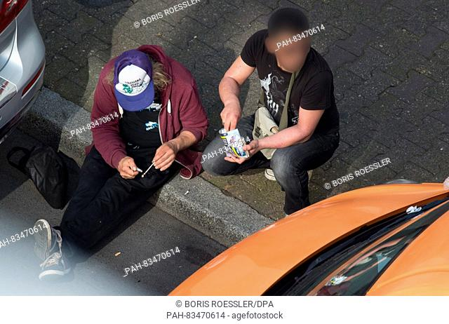 A drug addict preparing a crack pipe while a second man is looking out for the police on an open street in the central station area in Frankfurt/Main, Germany