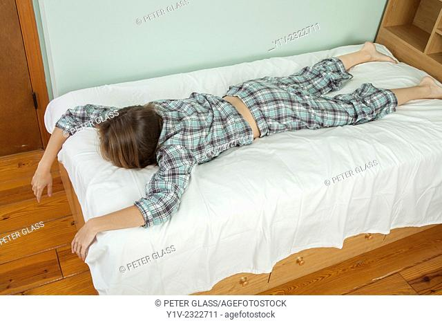 Young woman lying on her bed