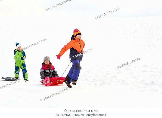 happy kids with sled having fun outdoors in winter