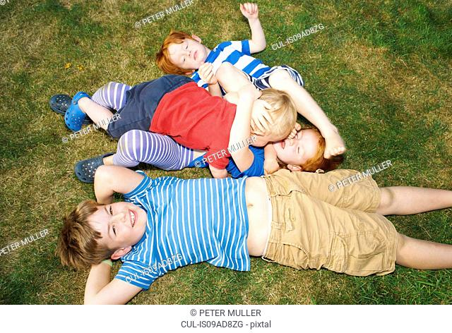 Three brothers and sister lying on grass in garden