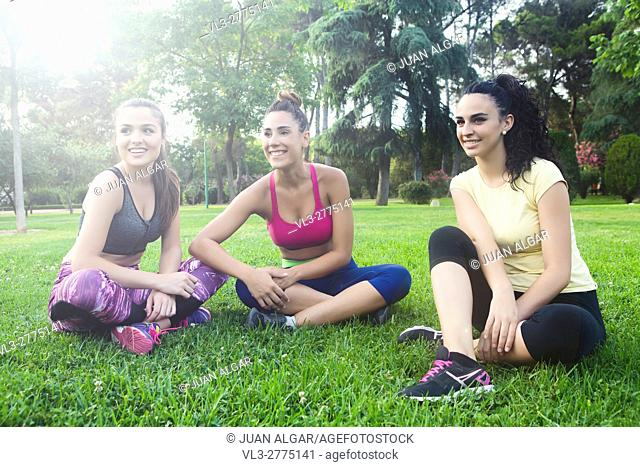 Happy sportswomen sitting with crossed legs on grass in park