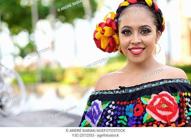 Young woman wearing traditional Mexican costume while smiling at camera. Puerto Vallarta, Jalisco, Mexico