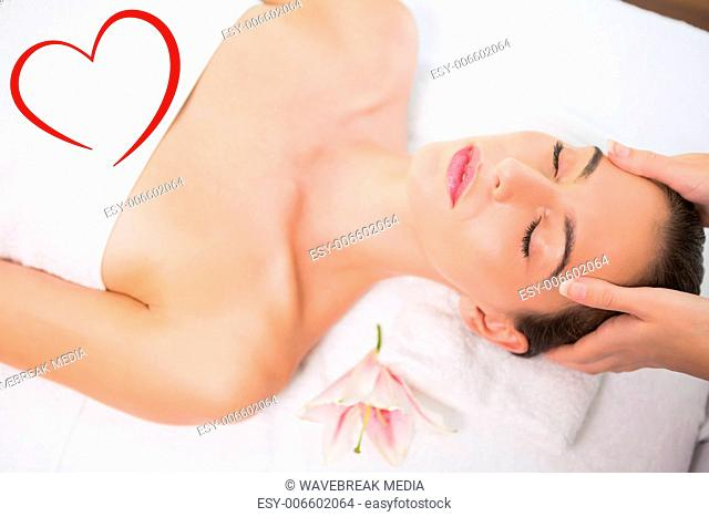 Composite image of attractive woman receiving head massage at spa center