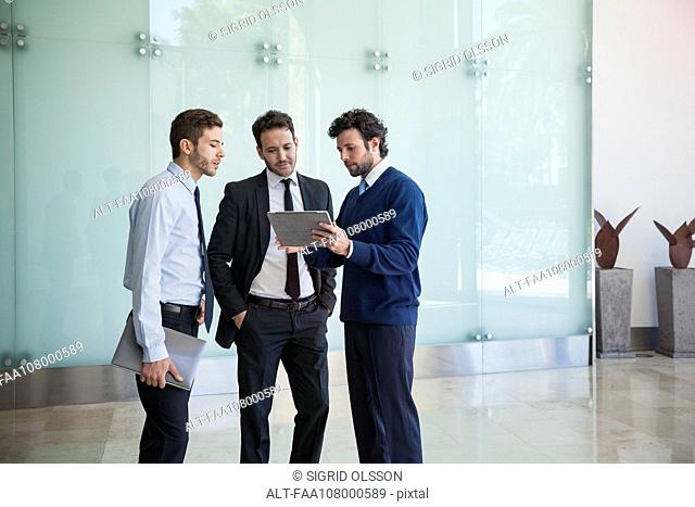 Businessman presenting idea to associates using digital tablet