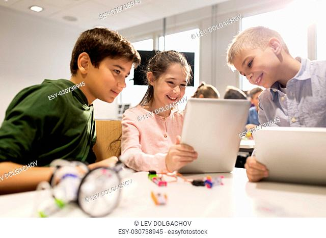 education, science, technology, children and people concept - group of happy kids or students with tablet pc computer programming electric toys and building...