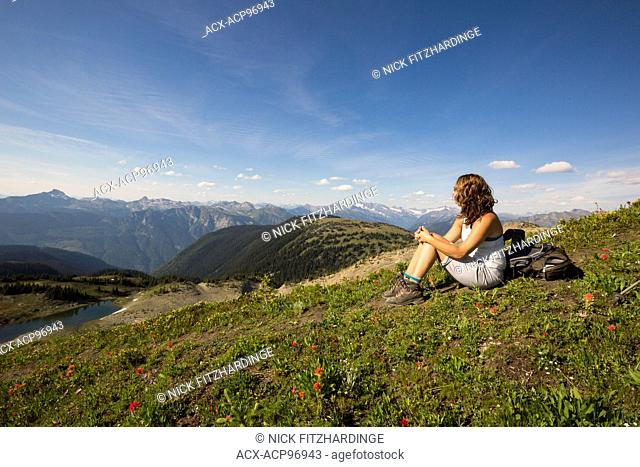 Female hiker sitting in alpine below the summit of Mt McCrae, Kootenay Region, British Columbia, Canada
