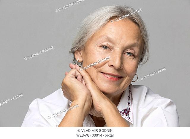 Portrait of relaxed senior woman with grey hair in front of grey background