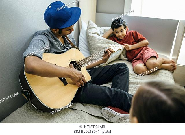 Mixed race boy watching brother playing guitar in bedroom