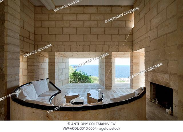 Can Lis, Mallorca, Spain. Architect: Utzon, Jorn, 1971. Living room with built in crescent shaped sandstone sofa. frameless windows and shaft of light entering...